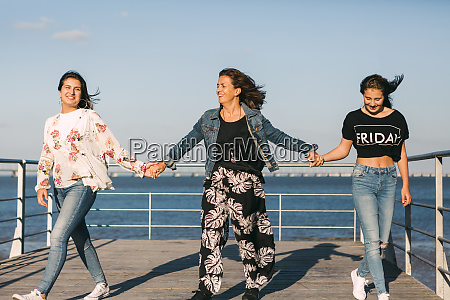 mother holding daughters hands while walking