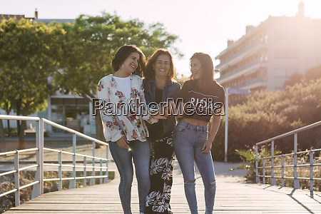 cheerful mother holding daughters hands while