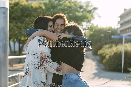 cheerful mother embracing daughters while standing