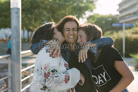 cheerful loving mother embracing daughters while