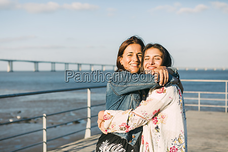 happy mother embracing daughter while standing