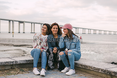 smiling mother with daughters sitting on