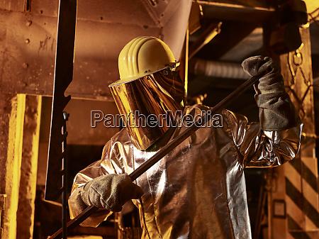 male worker holding metal rod in