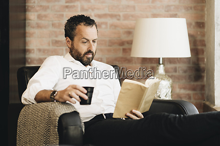 mature man sitting in armchair reading