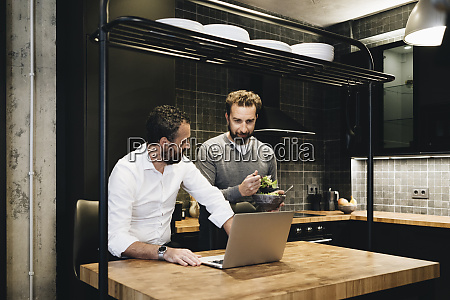 mature friends working on laptop in