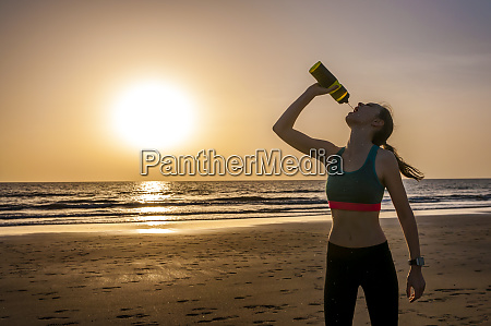 sporty woman drinking water at the
