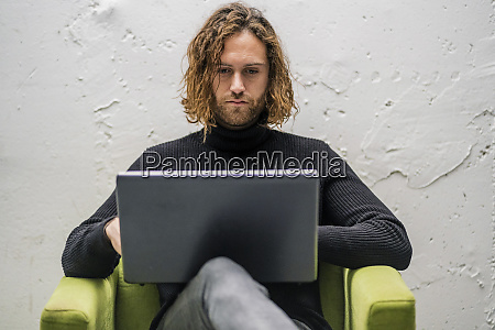 bearded young man using laptop while