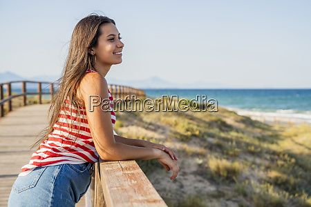 thoughtful teenage girl standing on boardwalk
