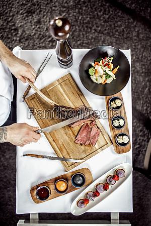 hands of chef slicing tomahawk steak
