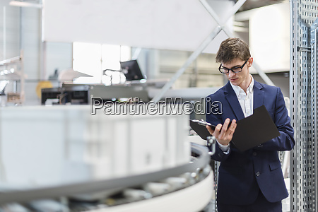 male manager holding file while standing