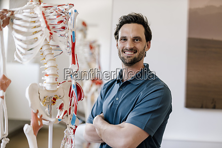 physiotherapist standing by anatomical skeleton with