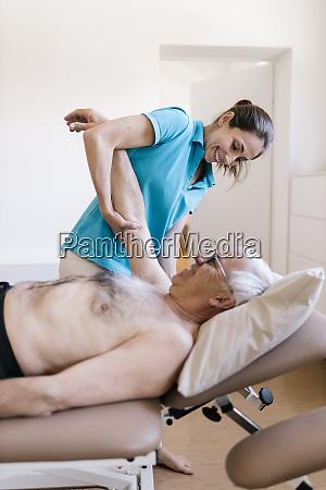 female physiotherapist giving treatment to senior