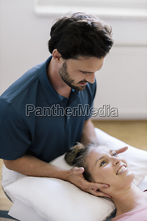 physiotherapist giving treatment to female patient