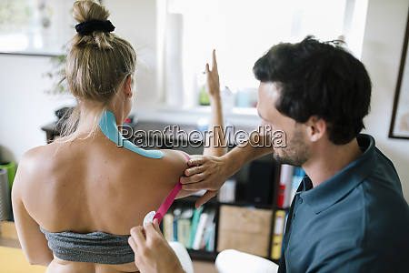 physiotherapist applying therapeutic tape on patients