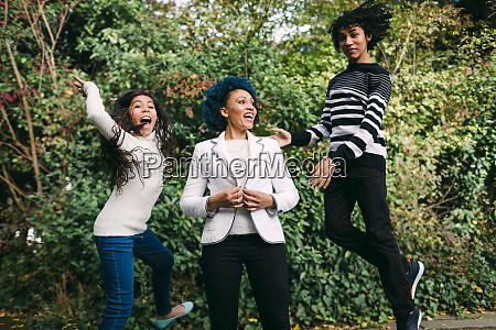 happy mother standing by children jumping