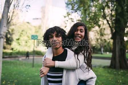 boy with curly hair piggybacking smiling