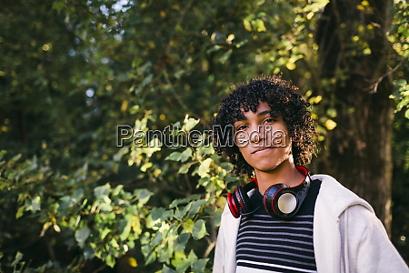 boy with curly hair standing against