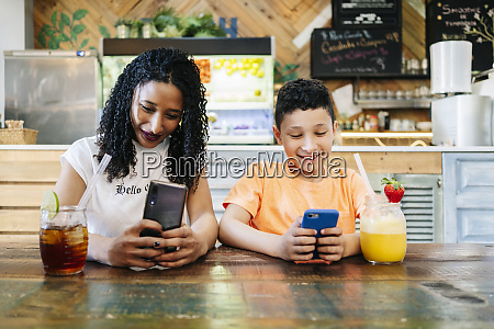 smiling mother and son using smart