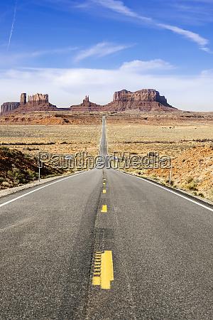 empty desert road towards famous rock