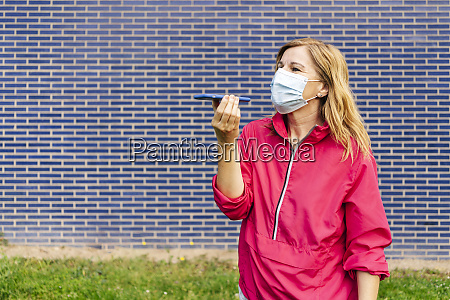 woman with surgical mask using smartphone