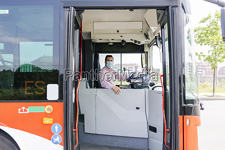 mature bus driver wearing protective mask
