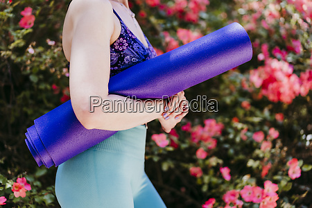 fit woman with purple yoga mat