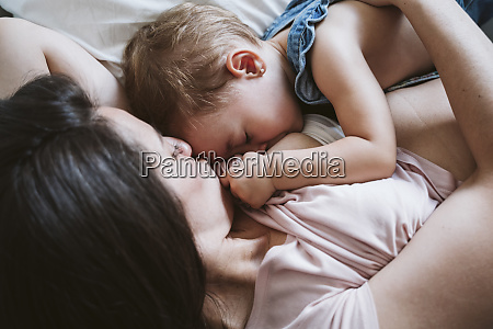 mother breast feeding baby girl on