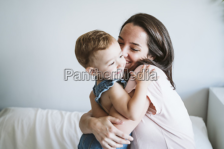 mother hugging baby girl at home