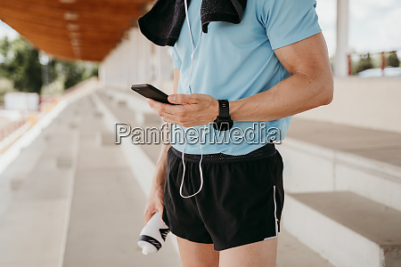 male athlete checking smartphone on grandstand
