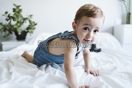 baby girl crawling on bed