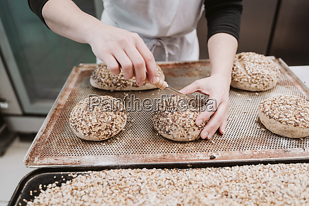 baker cutting wholegrain buns at bakery