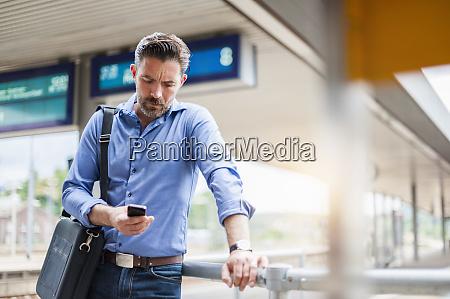mature businessman using smart phone while