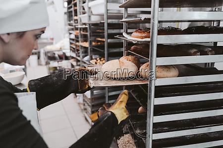 female baker inserting bun tray in