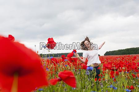 happy beautiful woman running on poppy