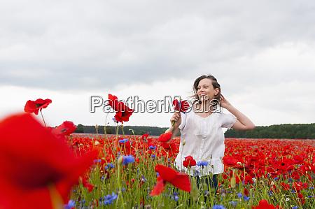 happy beautiful woman walking on poppy