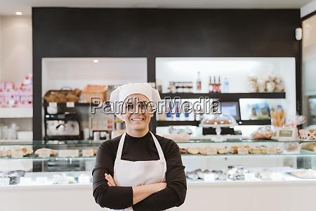 happy female baker standing arms crossed