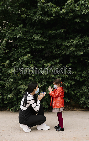 mother and daughter wearing masks while
