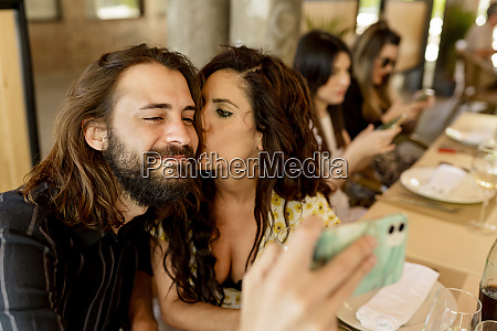 man taking selfie while woman kissing