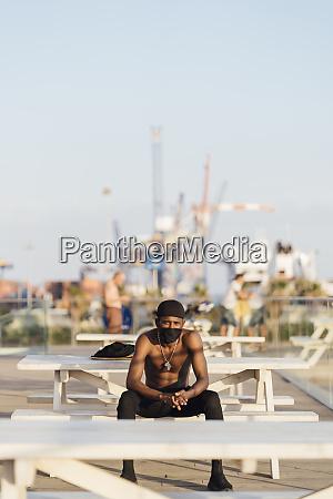 young man sitting shirtless on picnic