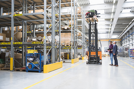 two men and worker on forklift