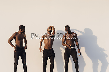 cheerful young male friends standing shirtless