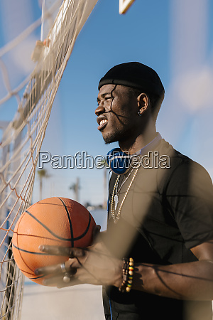 man holding basketball looking away while