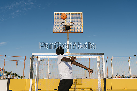 young man playing basket against blue