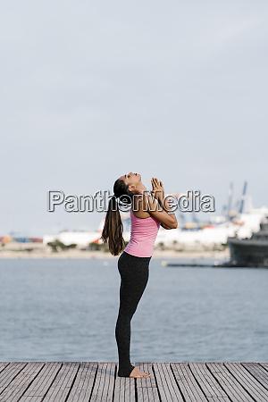 female athlete with eyes closed meditating