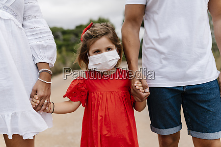 girl wearing mask while holding hands