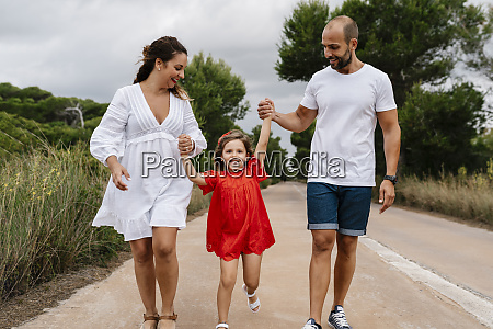 happy girl walking with parents on