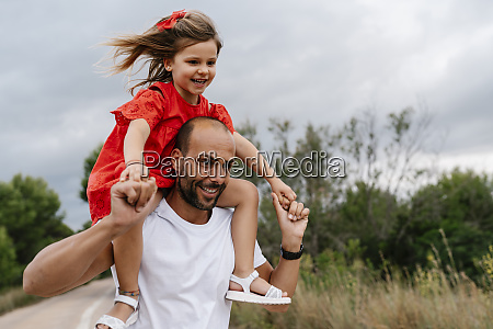 happy man carrying daughter on shoulders