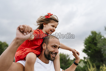 happy man carrying cheerful daughter on
