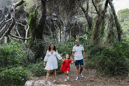 family walking on trail in forest