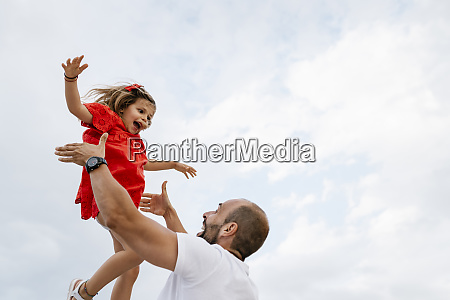 cheerful father lifting daughter against sky